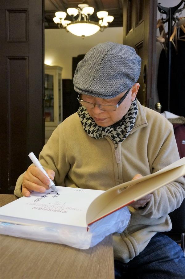 4画家张安朴在自己的作品集上签名_调整大小.JPG